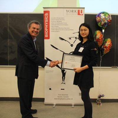 Kira Teramoto being congratulated by Marshall McCall, Chair of the Department of Physics and Astronomy .: