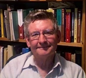Headshot of Martin Muldoon in front of his bookshelf