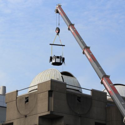 Crane lifting piece of telescope into dome