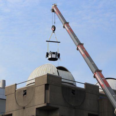 Crane lifting piece of telescope into dome