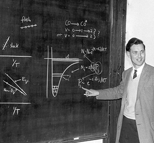 An early photo of Huw Owen Pritchard pointing to a blackboard
